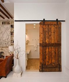 Salvaged Barn Door... or any door. I love the idea of a door on a slider like this. It saves space and is a great design element.