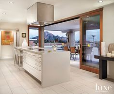The dramatic view from the kitchen expands to the patio via sliding wood-clad doors from Sierra Pacific Windows. Just outside, a dining set from Crate & Barrel provides al fresco seating. The center island and stainless-steel hood are part of a custom cabinet system by Poliform - Modern Love: An Inviting Space to Relax and Entertain   LUXE Source