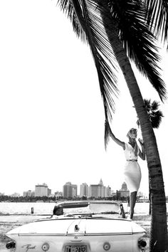 Black and white vintage photo of a woman standing on a car under a palm tree