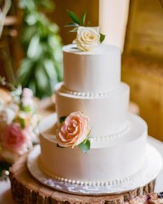 A simple white wedding cake served up on a tree slice for a rustic twist