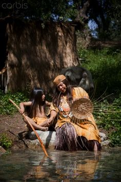 Traditions Teacher with Clapper Stick. Native American grandmother demonstrates the weaving of a traditional basket near a stream to her grandchild of the materials that would have been used by their ancestors now known as the Mission Native Americans of Orange County.Marilyn Angel Wynn photography