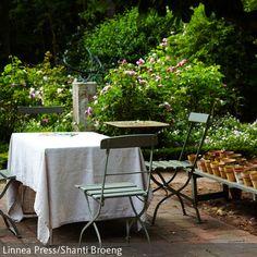 Diese Blumentopf-Deko im Garten ist eine tolle individuelle Gestaltungsmöglichkeit. Dazu runden die grünen Gartenstühle aus Holz zusammen mit der weißen  …