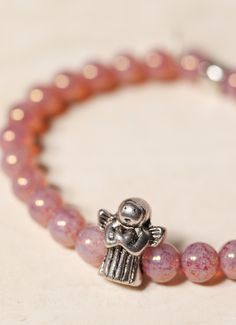 First Communion Gifts -Translucent pale rose beads encircle a silver guardian angel bead. A sweet bracelet to gift a young girl celebrating any special occasion as a symbol of the tender mercies of our loving God.