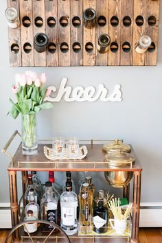 Don't banish your wine to a dark cabinet! Have your favorite bottles ready to go by mounting a storage rack near your bar cart.  Photo by Erin McGinn Photography via Style Me Pretty