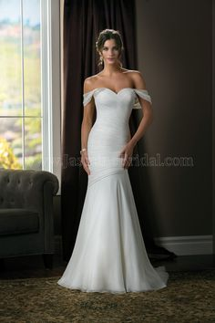 Jasmine Couture Wedding Dress Style T172004 in Ivory. Simple yet elegant, this is a dress for the sophisticated bride. The dress has a modern silhouette with its portrait neckline and fit and flare skirt, and the detailed ruching and beading of Jasmine's silk crinkle chiffon add up to a dress worthy of standing in the center of any wedding.