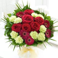 These red roses and germini mixed with green carnations are a majestic gift.
