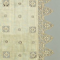 White linen table cover with rows of reticella squares in three sizes, each enclosing another square. Deep border of triangular points.