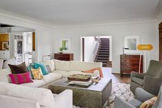 To make this outdated home feel livable and open, designer Michael Abraham brightened the interior with clean white walls and neutral furniture. Stainless appliances, faux-fur throws and vibrant accents throughout help the space feel calm and contemporary.