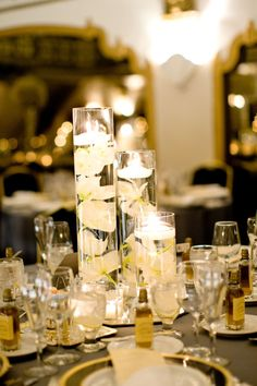 The other half of the short centerpieces will be a trio of cylinder vases at different heights with submerged white phalaenopsis orchid blooms and floating candles.  These will be surrounded by three more skinny cylinders with floating candles and mercury glass votives.