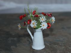 Hand Made Dolls House 1/12th Scale Wild Daisys and Poppies Flower Arangement  Made with great care and attention to detail this beautiful Artisan made Dolls House 1/12th Scale Wild Flower arrangement has been created using a White Enamel Painted Pewter Jug with a selection of hand-made Wild Daisy and Poppy flowers and foliage, etc.  All flowers are completely hand made and are on wires so can be re-arranged.  It looks very realistic, and would be great addition to your dolls house....
