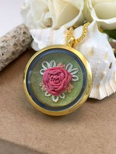 How gorgeous is this necklace? A delicate hand embroidered rose in bloom, preserved behind glass. This gold circular glass locket pendant necklace features a pink silk ribbon rose with white leaves and peach buds on 100% pure light green wool felt.