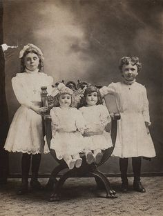 Girls with huge dolls seated on a chair