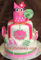 Two tier custom designed girl's pink and green fondant owl and lollipops birthday cake