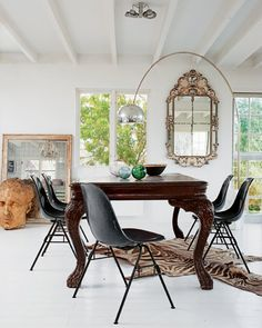 eclectic dining room with Eames chairs, vintage Arco lamp by Flos, antique dining room table, flea market mirror, in the home of designer Marie Olsson Nylander
