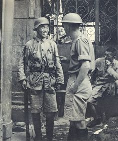 Chinese and British soldier in conversation during 1937 battle of Shanghai.