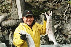 Media Gallery | Nisga'a Lisims Government Nisga'a Fisheries Nisga'a Fisheries worker on the Nass River holding up two salmon.