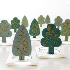 3D-Minikarten Forest von Jurianne Matter - 9,50€ Das entzückende kleine Wäldchen aus 10 golden gesprenkelten Bäumchen von Jurianne Matter. Die Kärtchen funktionieren wie kleine Etuis - sie lassen sich in der Mitte falzen und mit einer Lasche verschließen. So entsteht eine kleine, an den beiden kurzen Seiten offene Hülle, in die sich kleine Kärtchen - z. B. Namens- oder Visitenkarten - schieben lassen. Natürlich können Sie die Kärtchen auch direkt beschriften.