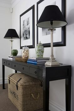 Chic foyer features seagrass trunk tucked under black console table with 5 drawers topped with silver lamps accented with black lamp shades, white and green ginger jar, books, seagrass tray and glass canister filled with seashells. Decor, Table Style, Black Sofa Table, Console Table Styling, Interior, Entryway Decor, Home Decor, House Interior, Home Deco