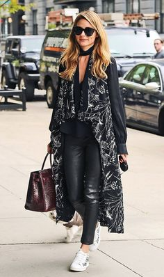 Olivia Palermo gives an all black look an original twist by pairing her leather pants and black blouse with a patterned long vest and white Moncler sneakers