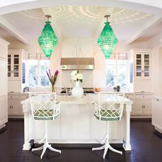 Jade chandeliers + fun bamboo barstools liven up a white kitchen. Great space layout too.
