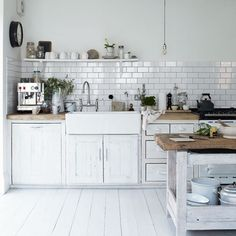 pretty much everything i want in a kitchen!! white kitchen bare bulbs subway tiles white floor boards rustic bench tops the tapware the black french school clock!