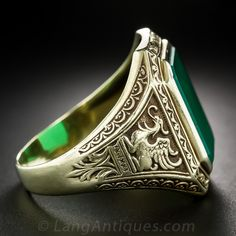 A pair of vigilant griffins perched atop neo-classical columns guard a large and glowing dyed green emerald-cut chalcedony in this handsome, rare, large scale and highly-distinctive vintage gent's ring, elegantly crafted in rich 14 karat gold. Ring measures 7/8 inch by 3/4 inch, in a finger size 13.