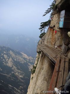 "Huashan1: Mount Huashan, aptly called the ""Mountain of Death', in the Shaanxi province of China, extends to meet the clouds at 6,800 feet.  You can enjoy the best tea in China at the top if you're willing to climb that height while risking your life. It's an impossible feat some people have not lived to finish because the top of the mountain is almost inaccessible with a rickety trail of boards (2 feet) circling the mountain which sometimes slopes downward. Clinging onto chains precariously…"