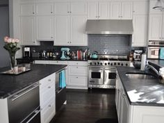 i love the contrast of the white cabinets with the dark floors and counters. the light blue accents are nice too!