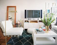 March April 2011 Issue - A square white coffee table and a white chair beside a brass floor lamp