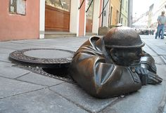 "MAN AT WORK, BRATISLAVA, SLOVAKIA  Coming out of a street manhole, this funny looking man was sculpted back in 1997. After several automobiles smashed into the durable statue, a sign was added as warning of his presence. It reads: ""Man at Work."""