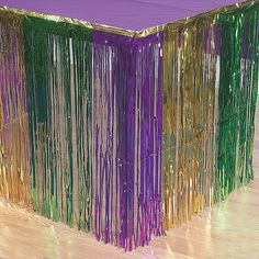 """Fringe Mardi Gras Table Skirt. Add some sparkle to any party table with this metallic foil table skirt! In a festive green, purple and gold, this shimmering table decoration will complete your Mardi Gras celebration! 9 ft. x 29"""""""