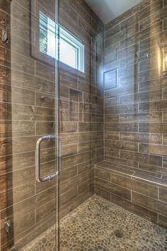 Faux wood plank shower wall tile and pebble shower floor tile #woodtile #pebble #rustic #coastal