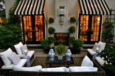 elegant patio seating area. black and white cabana stripe awnings.