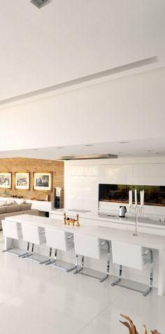 Blonde wood panels soften the stark white gloss kitchen.