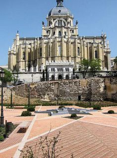 Firstly, remains of the old Arab wall. In the background, the Almudena Cathedral from the side of the crypt. Cuesta de la Vega, Madrid, Spain