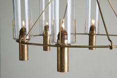"The Oliver Chandelier is the perfect balance of elegant and industrial, comprised of a circle of six spring-loaded brass candleholders with 8"" glass cylinders. The spring-loaded feature allows for ease of use and replacement of its dripless wax candles."