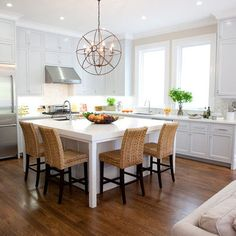 White L-shaped kitchen with stainless appliances, large window(s) above the sink, our island would be smaller but the layout is perfect!