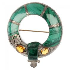 A late Victorian silver Scottish brooch, of circular outline inlaid with malachite and two oval orange paste stones, with engraved scrolling decoration and applied buckle detail / Estimate £100 – £150