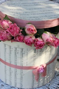 Hatbox covered with sheet music and embellished with silk rose.