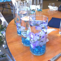 Centerpieces at my sisters wedding: one vase ($1.18), one bells of Ireland  off of a vine-like strand from local craft store ($12.99; makes 12), and glass beads (1.18; makes 2) with a little water. And they looked great!