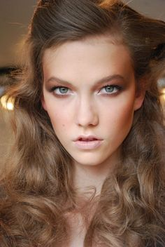Karlie Kloss with long curly hair for a runway show.