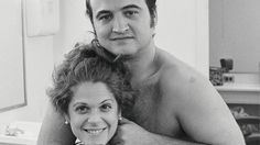 Gilda Radner and John Belushi share a tender moment in the hair and makeup room. (1976)