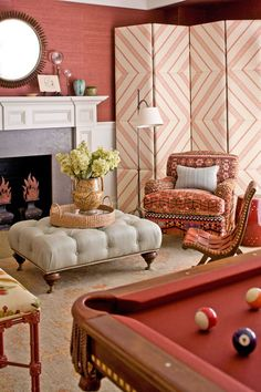 An Office & A Gentleman. The classic burgundy of a pool table's felt is the inspiration for this billiard room. Fiery reds appear in the grasscloth wall covering, , Kilim-covered club chairs, and geometric folding screen. Interior Designer: Carrier and Company.