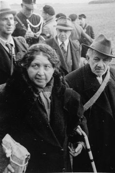 An elderly Jewish couple en route to the Westerbork transit camp. A Dutch policeman stands beside the group, overseeing the deportation.