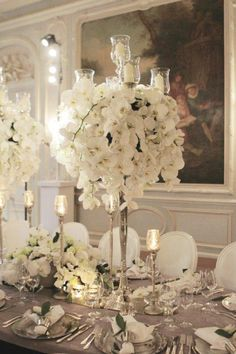 LOVE the monochromatic white floral arrangement  - ALSO - the height of the centerpiece - important - not to affect site line of those sitting / talking around the table - does not interfer