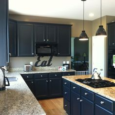 Black kitchen cabinets. We painted our maple wood cabinets  BM Jet black.