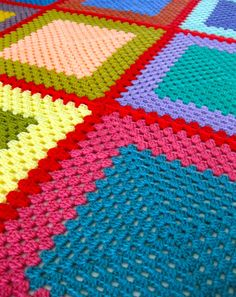 Giant granny squares crochet blanket, 10 rows color 1, 5 rows color 2.  Bright and bursting with colour, my youngest claimed this blanket. One square a day, twelve in total, outlined in red and bordered in brown. A mix of 100% wool and acrylic!