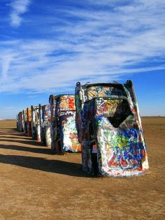 Just west of Amarillo, Texas, 10 sets of graffiti-covered tail fins stand as a tribute to the American dream. The art installation, known as Cadillac Ranch, features 10 classic cars, half buried nose first at the same angle as the Great Pyramid in Egypt. - [someone else's caption]