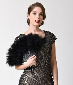 Dramatic plumage to add to your elegant ensemble. With 21 decorative black staves that lead up to soft black marabou feathers. Held together with a metal U-ring and accented with a charming black tassel.<br />Available while supplies last.