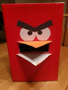 Angry Birds Valentine card box. Cut out slot in box lid. Paint 2 triangle pieces of cardboard orange for beak. Cut 2 slits on top & bottom of mail slot just big enough for beak to fit in. Cut construction paper for eyes & brows. Ready for Valentines!
